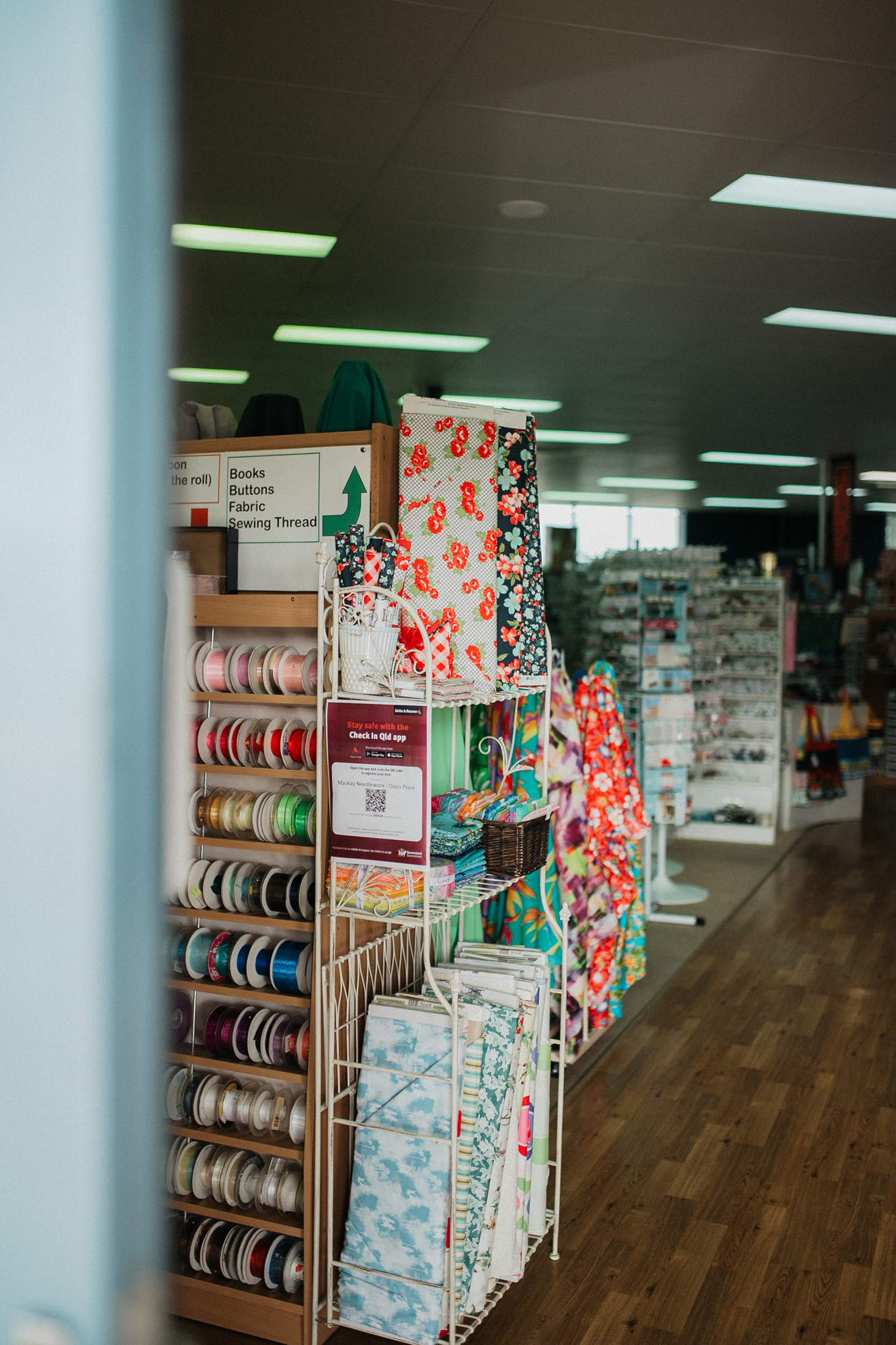 Entry of Needleworx store with rows of fabric