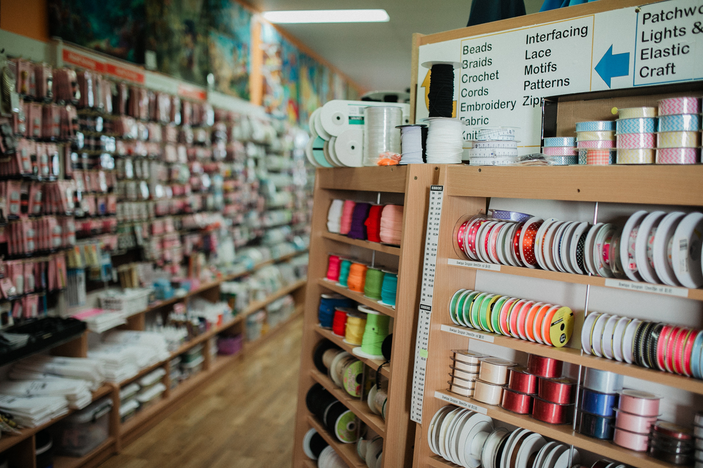 Needleworx store with rows of fabric and sewing material and ribbon