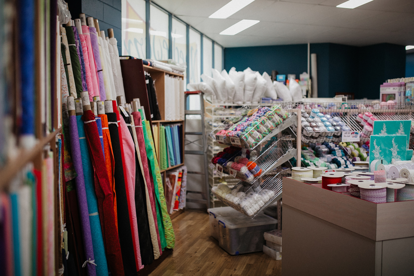 Needleworx store with rows of fabric and sewing material and wool