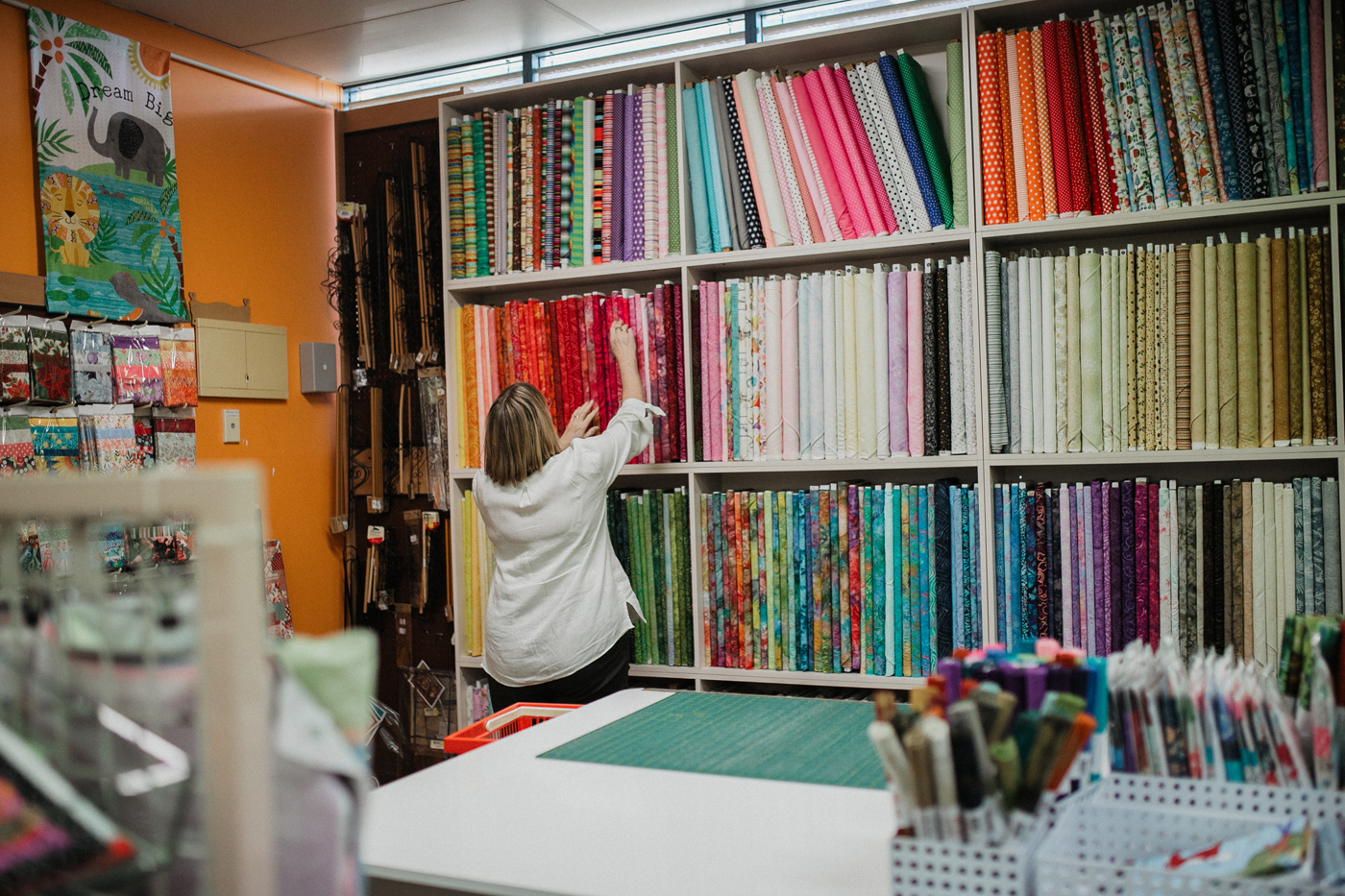 Needleworx staff browsing rows of fabric swatches