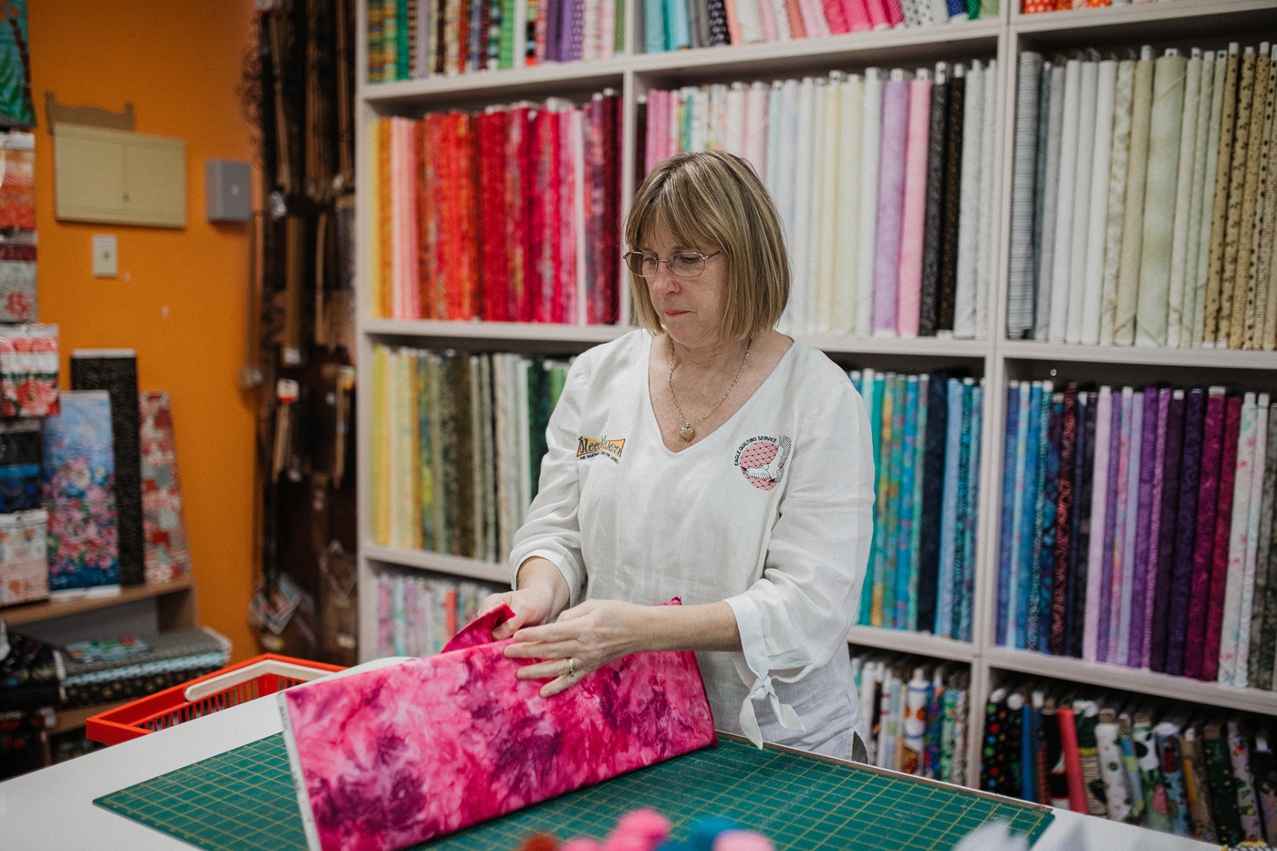 Preparing bright pink fabric sewing material with rows of fabric swatches in background